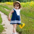 Stock Photo: Girl in a dark blue dress near a field of blossoming sunflowers