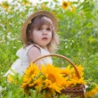 Little girl with a basket with sunflowers — Stock Photo #12757920