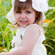 Little girl in a white dress and a hat among sunflowers — Stock Photo #12757930