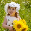 Little girl in a white dress and a hat among sunflowers — Stock Photo
