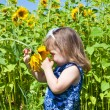 Girl in dark blue and sunflowers — Stock Photo #12757967