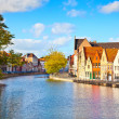 Постер, плакат: Colourful old houses reflected on water at Brugge Belgium