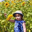 Girl in dark blue and sunflowers — Stock Photo #23385618