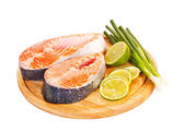 Two raw salmon steaks with lime and green onion on the cutting b — Stock Photo