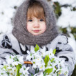 Little girl in a winter wood with the big basket of snowdrops — Stock Photo #37401093