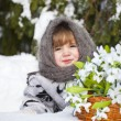 Little girl in a winter wood with the big basket of snowdrops — Stock fotografie
