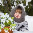 Little girl in a winter wood with the big basket of snowdrops — 图库照片