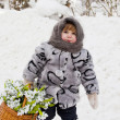 Little girl in a down scarf, a fur coat and valenoks bears a bi — Stock Photo