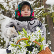 Little girl in a winter wood with the big basket of snowdrops — Stock Photo #37401211