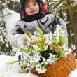 Little girl in a winter wood with the big basket of snowdrops — Stock Photo #37401213