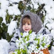 Little girl in a winter wood with the big basket of snowdrops — Stock Photo #37401347