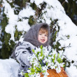 Little girl in a winter wood with the big basket of snowdrops — Stock Photo #37401351