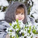 kleines Mädchen in einem Winter-Holz mit den großen Korb von Schneeglöckchen — Stockfoto #37401371