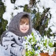Little girl in a winter wood with the big basket of snowdrops — Foto de Stock