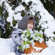 Little girl in a winter wood with the big basket of snowdrops — Stock Photo