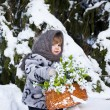 Little girl in a winter wood with the big basket of snowdrops — Stock Photo #37401387