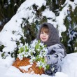 Little girl in a winter wood with the big basket of snowdrops — Stockfoto