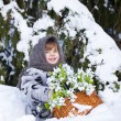 Little girl in a winter wood with the big basket of snowdrops — Stockfoto #37401393