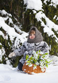 Little girl in a winter wood with the big basket — Stock Photo