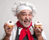 Smiling chef with Hanukkah doughnuts — Stock Photo