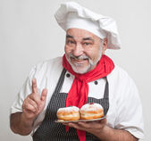 Smiling chef with Hanukkah doughnuts — Stock Photo