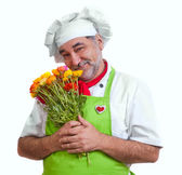 Smiling attractive chef with flowers — Stock Photo