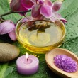 Oil and orchid with green leaf - Photo
