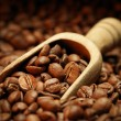 Coffee beans and wooden scoop — Stock Photo