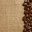 Coffee beans on burlap texture — Stock fotografie #15555143
