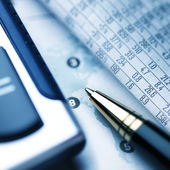 Calculator and pencil on newspaper — Stock Photo
