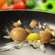 Raw egg falls on the pan - Stock Photo