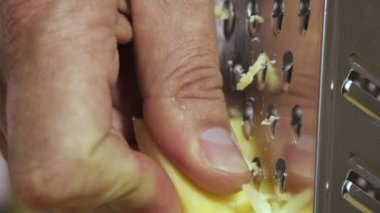 Hand grating yellow cheese with a metal grater closeup — Stock Video