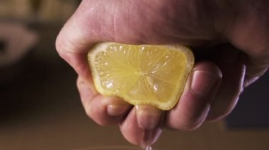 Hand squeezing lemon on dark background — Stock Video
