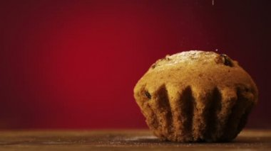 Muffin cake with white powdered sugar on red — Stock Video