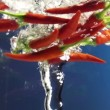 Chili peppers dropped in water vortex on color background — Stock Video #24070399