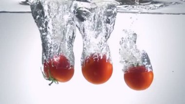 Fresh tomato dropped into water with bubbles — Stock Video