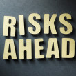 Stock Photo: Word Risks Ahead on paper background