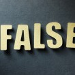The word False on paper background — Stock Photo #32520125