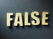 слово false на фоне бумаги — Стоковое фото
