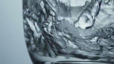 Close up veiw of clean fresh water swirling around the bottom of transparent glass — Wideo stockowe