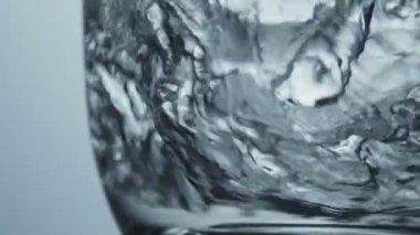 Close up veiw of clean fresh water swirling around the bottom of transparent glass — Stok video