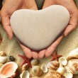 Hands holding a heart-shaped stone — Stock Photo