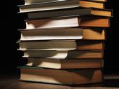 Pile of hardcover books in a shadowy room — Stock Photo