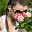 Stock Photo: Beautiful girl sniffs scent of roses