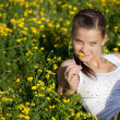 Beautiful girl lying in a field of flowers — Stock Photo