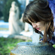 The girl drinks water from a fountain — Stock Photo