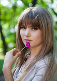 Portrait of a beautiful young girl in a park with flower in hand — Stock Photo