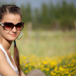 Portrait of a beautiful girl in sunglasses on a yellow-green mea — Stock Photo