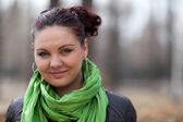 Portrait girl in a green scarf in the park — Stok fotoğraf