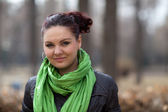 A girl in a green scarf in the park — Stock Photo